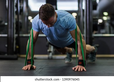 Man doing push-up using a elastic band at the gym.
