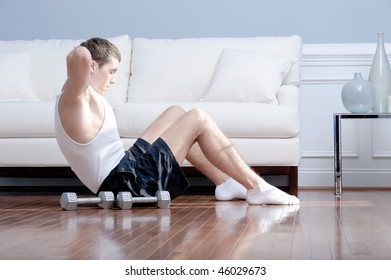 Man doing push-ups next to couch, with arm weights lying on the floor next to him. Horizontal format.