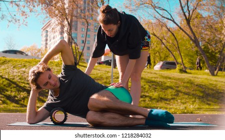 Man doing self massage of the body with a roll. Woman teaching and correcting him. Sunny day, golden autumn