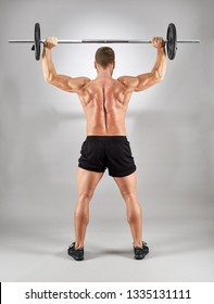 Man doing shoulder workout with barbell on gray background