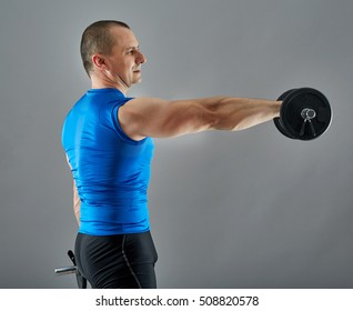 Man doing shoulder workout with dumbbell over gray background
