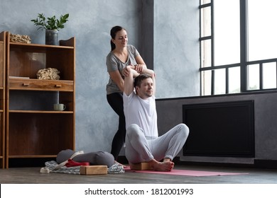 Man doing shoulders stretching, yoga exerise. Female teacher helping him to stretch muscles. Partner yoga, flexibility concept