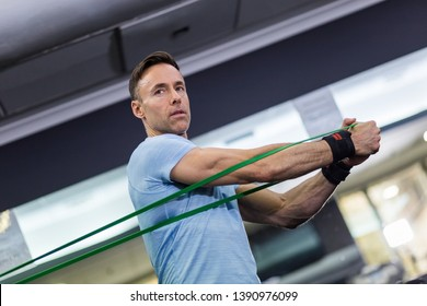 Man doing side-to-side chops exercise with elastic band at the gym.
