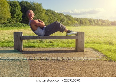 Man doing sit ups on a bench outdoors/Outdoor situps/Fitness photography