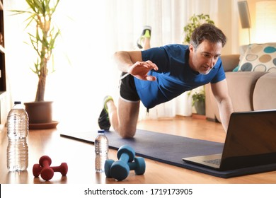 Man doing sports on a mat watching videos on a laptop in the living room with water and dumbbells on the floor