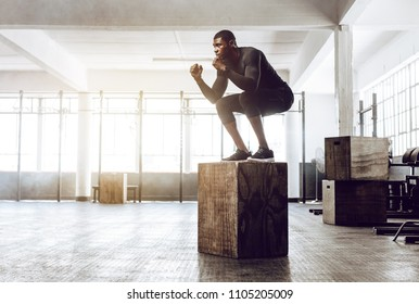 Man doing squats on a squat box at the gym. guy at the gym working out standing on a wooden squat box.