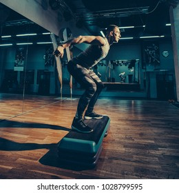 Man doing step up jumps in health club. Toned image. The man is exercising his legs on the stepper. doing steps from the side view