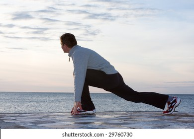 Man doing stretching exercises at the sea