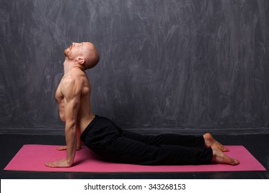 Man doing stretching. A man with a naked torso doing yoga cobra on black background.