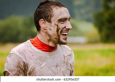 Man Doing a Tough Mudder event, caked in mud and wet through, taking a break and having a laugh at a friend off camera. Facing right profile with the fields in the background