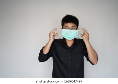 The man doing wearing face hygienic mask for prevention global covid-19 virus pandemic. The corona-virus from wuhan is dangerous. Use his hands pull mask into face.