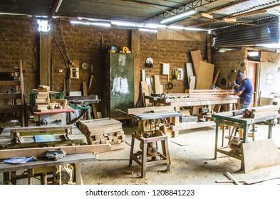 Man doing woodwork in carpentry. Carpentry workshop. Carpenter working on wood plank in workshop.