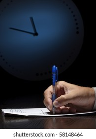 man doing written test with the clock in the background, low key, useful for job application.education and other testing related themes