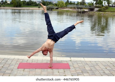 Man doing yoga asanas and acrobatics in the park