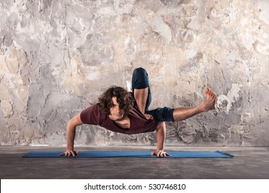 Man doing yoga exercises. Practicing yoga in a urban background