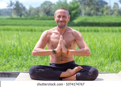 Man doing yoga and meditating in a position near a green rice terrace on the tropical island of Bali, Indonesia. Close up