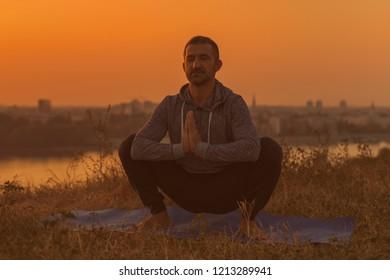 Man doing yoga on sunset with city view,Utkatasana/Buddhist stupa pose .Toned image.