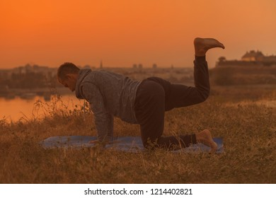 Man doing yoga on sunset with city view,Vyaghrasana/Tiger Pose.Toned image.