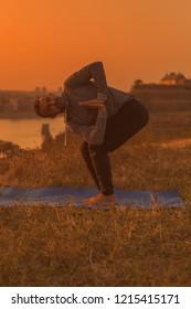 Man doing yoga on sunset with city view, Revolved Chair Pose  /Parivrtta Utkatasana.Toned image.