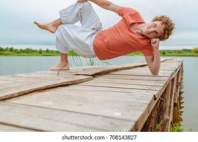 A man doing yoga on wooden pier at the lake