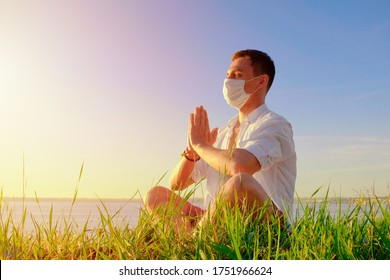 man doing yoga sitting in a lotus pose wearing PPE face mask. workout outdoors post quarantine. coping with panic, anxiety, global pandemic. safety measures covid-19. new crisis regulations reality. - Shutterstock ID 1751966624