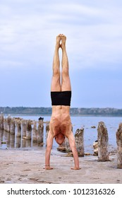 man doing yoga standing on hands on pristine beach