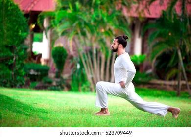Man doing yoga in tropic jungle