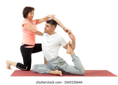 man doing yoga under the guidance of a trainer
