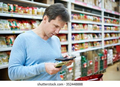 Man with dollars and calculator considers costs in the store