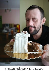 man with down syndrome holding cake