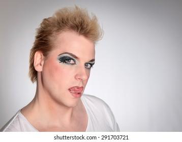 Man with drag make-up licking his lips looking at the camera