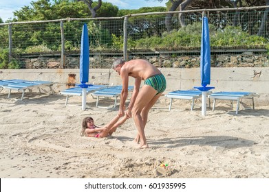 Man dragging daugher on the beach. Holiday and family concept.