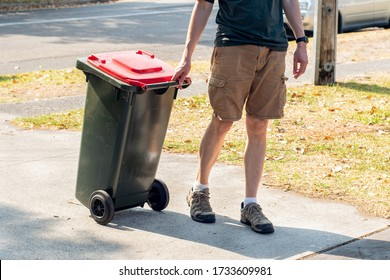 A man dragging the household wheelie red bin with general waste on the street for council gargbage collection. Waste management concept.