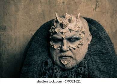 Man with dragon skin and beard. Monster face with white eyes, sharp thorns and warts. Demon head with grey collar on abstract beige wall. Alien or sorcerer makeup. Horror and fantasy concept.