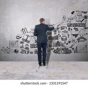 Man drawing a business plan on a concrete wall