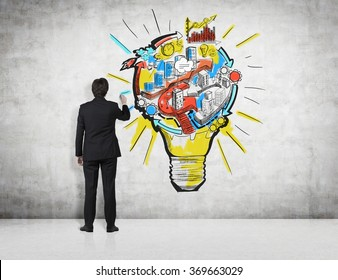 man drawing a coloured picture of a bulb with stages of organizing a business process in it. Concrete background. Back view. Concept of running a business.