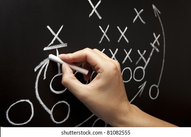 Man drawing a game strategy with white chalk on a blackboard.