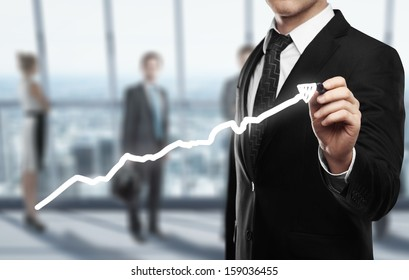 man drawing graph on office background