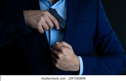 Man drawing his gun from coat pocket