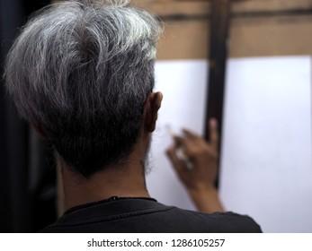 Man drawing on white paper.