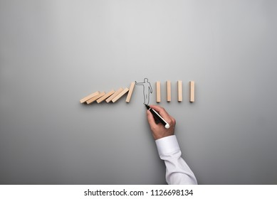 Man drawing the outline of a businessman stopping the domino effect in a conceptual image on gray background.