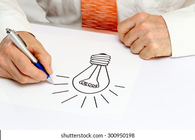 man is drawing a symbol on white paper