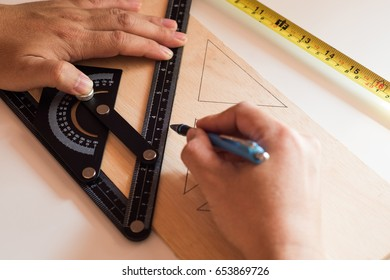 Man draws design, geometric shapes by pencil on wooden boards, wish Ruler and measuring tape.