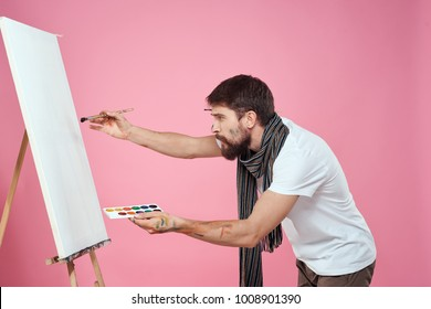 man draws on canvas on a pink background