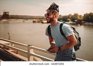 Man with dreadlocks and beard using phone by the river on a hot summer day