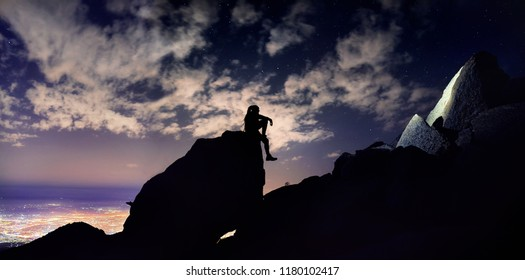 Man with dreadlocks sitting on the rock in silhouette at night sky with stars and glowing city light background.