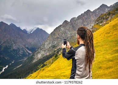 Man with dreadlocks taking photo with his phone in the mountains. Travel Lifestyle concept adventure active vacations outdoor