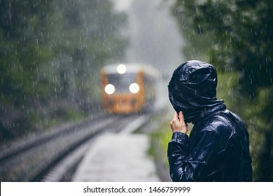 Man in drenched jacket standing on platform of railway station against train in heavy rain.