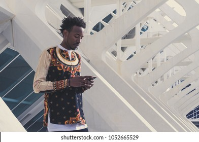 man dressed in african clothes consults his smartphone in a mode