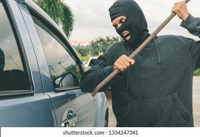 Man dressed in black with a balaclava on his head breaking a glass in car with crowbar. Car thief, car theft concept
